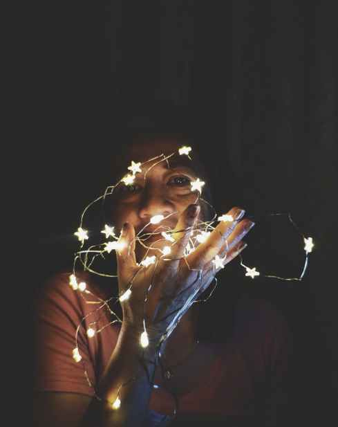 close up photo of a woman holding string lights